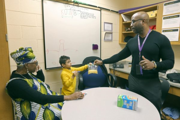 Therapist Andre Black met with 6-year-old Jamil Holley Jr. while Moukam observed.